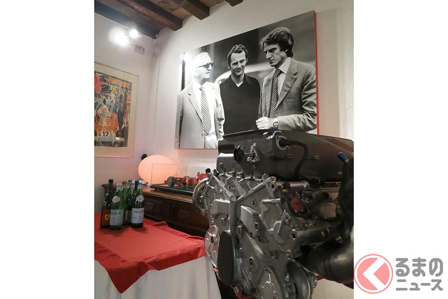 フェラーリの本物のエンジン、そしてモンテゼーモロとラウダと一緒に撮影されたエンツォの写真パネル